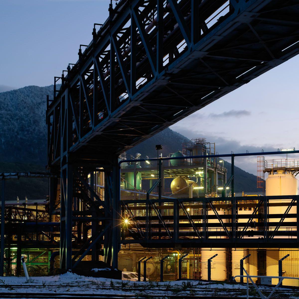 Usine chimique de nuit, sous la neige, avec montagne en fond